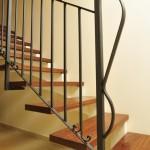 מדרגות מדורגות מברזל, חיפוי עץ ומעקה מתכת.